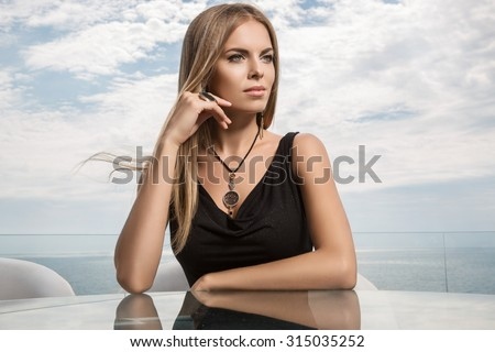 Portrait of elegant woman sitting in restaurant outdoors - stock photo