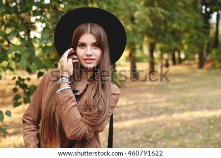Portrait of elegant woman wearing brown suede jacket and black hat. Autumn color, fall fashion