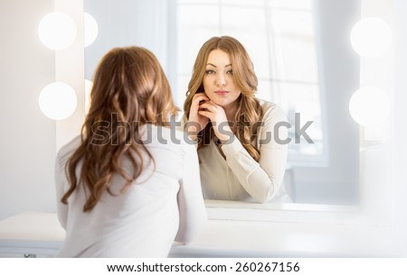 Portrait of elegant woman with curly hair looking at reflection in mirror - stock photo