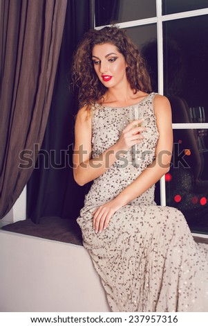 Portrait of elegant young girl with a champagne glasses at celebration indoor