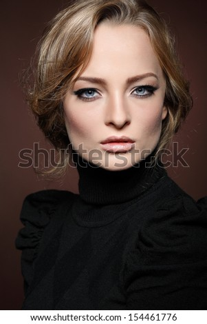 Portrait of elegant young woman in a black jumper  on a brown background - stock photo