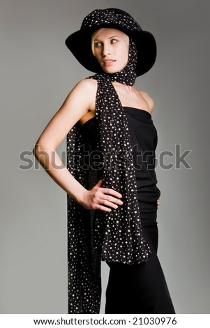 Portrait of elegantly dressed female in retro black evening gown and scarfed head with hat on it