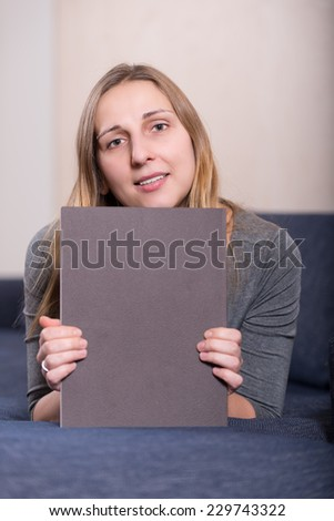 Portrait of elegantly dressed young brunette woman with magazine - stock photo