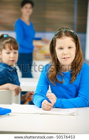 Portrait of elementary age schoolgirl sitting at class looking at camera, with other student and teacher in background. - stock photo