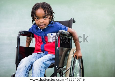 Portrait of elementary handicapped boy against board in classroom - stock photo