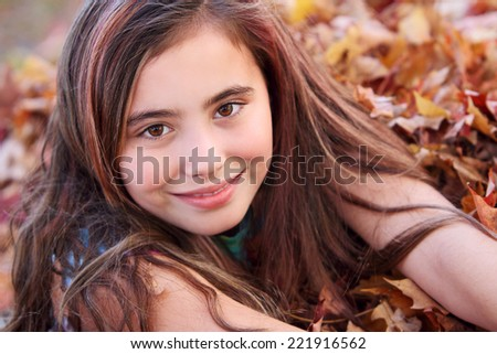 Portrait of eleven year old girl smiling in leaf pile. - stock photo