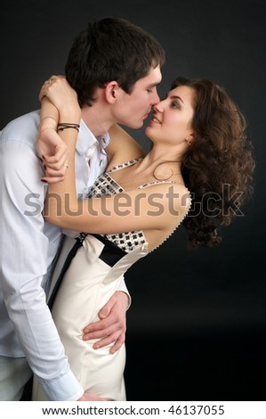 Portrait of embracing beautiful sexual couple over black - stock photo