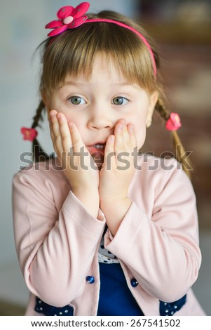 Portrait of emotional little girl sitting on a chair in a blue dress with a pink cape.