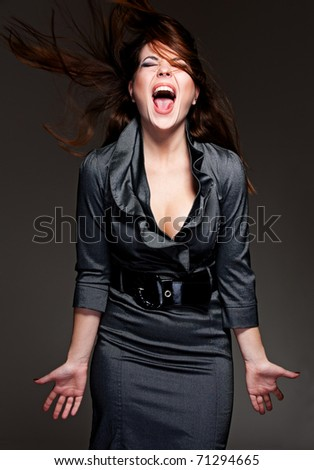 portrait of emotional woman over dark background - stock photo