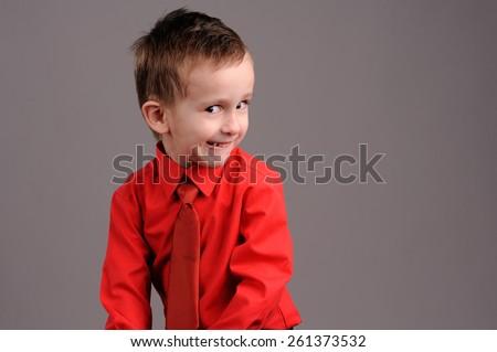 Portrait of emotionally kid. Emotional boy on the grey background - stock photo