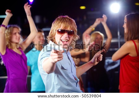 Portrait of energetic dancer on background of happy friends having fun