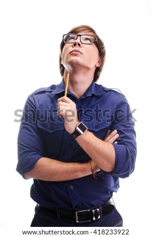 portrait of engineer in glasses with pencil in his hand looking at the sky and lost in thought on white background - stock photo