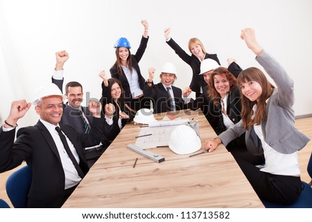 Portrait Of Engineers Sitting At Table Cheering