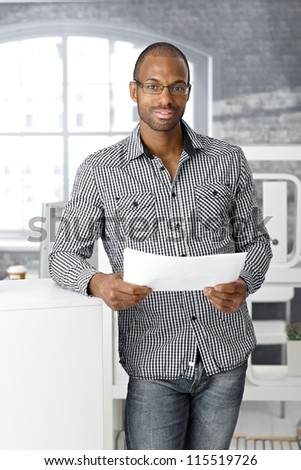 Portrait of ethnic office worker smiling, standing with document handheld, looking at camera. - stock photo