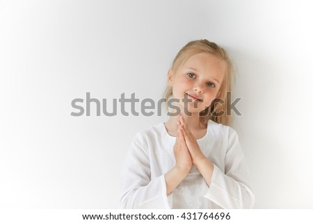 Portrait of European blond kid smiling and folding hands like a prayer. Her total white look and charming face show her positive emotions, purity, simplicity, friendly attitude and peace. - stock photo