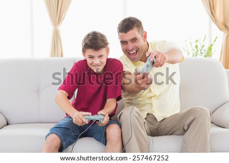 Portrait of excited father and son playing video game on sofa at home - stock photo