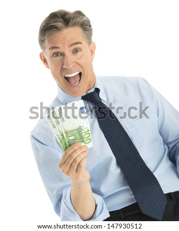 Portrait of excited mature businessman showing euro banknotes while standing against white background