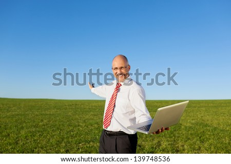 Portrait of excited mature businessman with arms outstretched holding laptop on filed against clear sky - stock photo