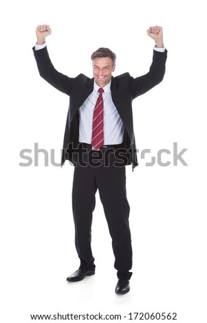 Portrait Of Excited Mature Businessman With Hand Raised