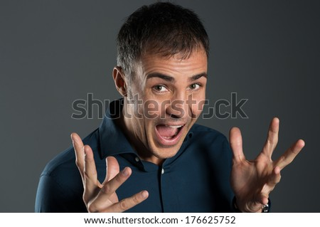 Portrait Of Excited Mature Man Screaming On Grey Background - stock photo