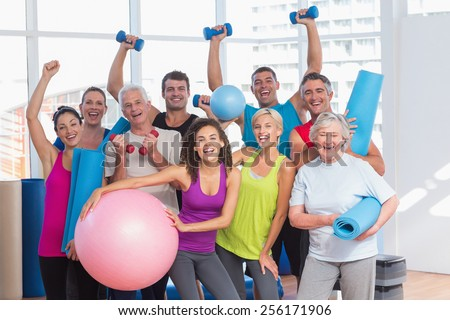 Portrait of excited people holding exercise equipment at health club - stock photo