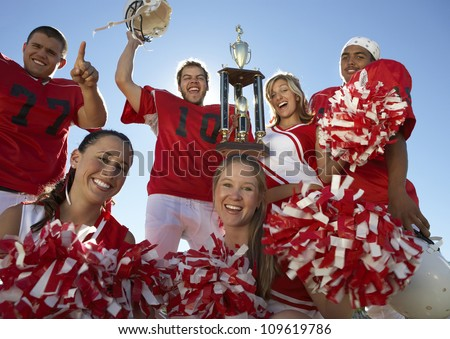 Portrait of excited players with cheerleaders holding trophy against clear sky - stock photo