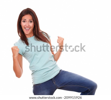 Portrait of excited pretty woman on blue t-shirt and blue jeans celebrating her victory while smiling at you with funny face and standing on isolated studio - stock photo