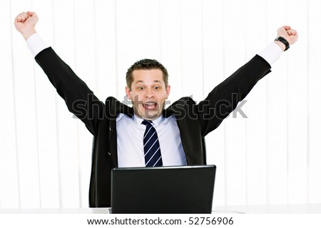 Portrait of excited young businessman with hands raised using laptop