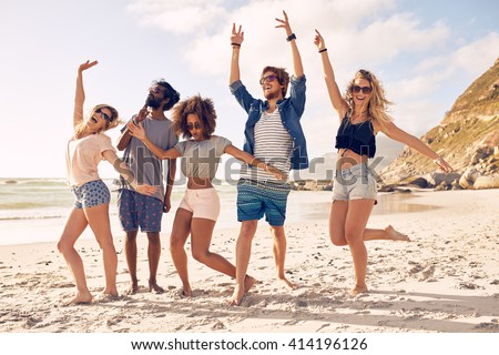 Portrait of excited young friends standing on the beach. Multiracial group of friends enjoying a day at beach. - stock photo