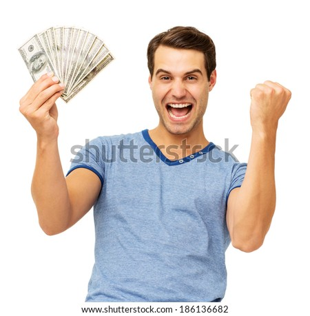 Portrait of excited young man clenching fist while holding US currency over white background. Horizontal shot. - stock photo