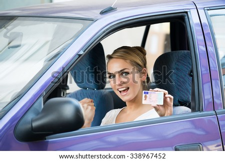 Portrait of excited young woman showing license while sitting in car - stock photo