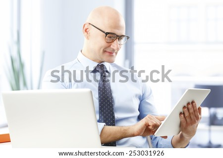 Portrait of executive business man sitting at desk and touching digital tablet.