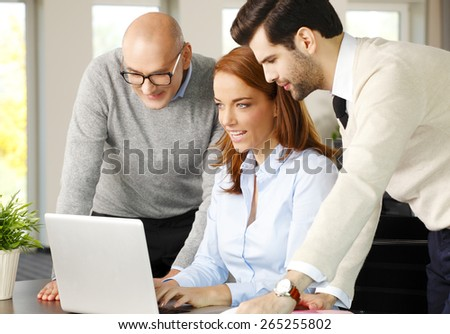 Portrait of executive business woman consulting with her business team while sitting at desk in front of computer. Teamwork at office.