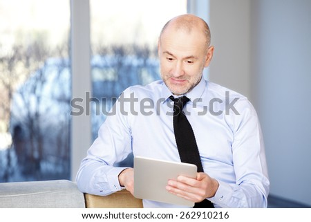 Portrait of executive businessman sitting at office and working on digital tablet. Business person analyzing financial data. - stock photo