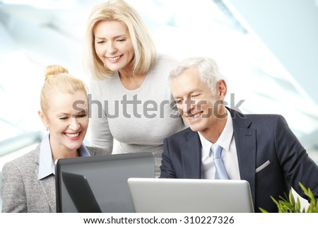Portrait of executive businessman sitting with businesswomen and consulting. Business people working together on laptop while sitting at meeting.  - stock photo