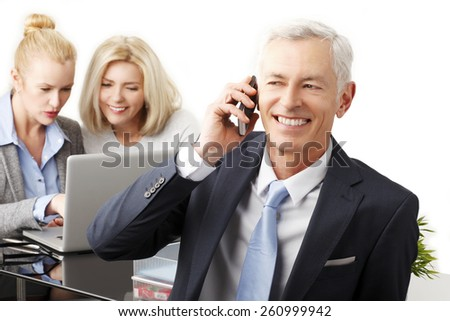Portrait of executive businessman using his phone while business team working at background. Isolated on white background.  - stock photo