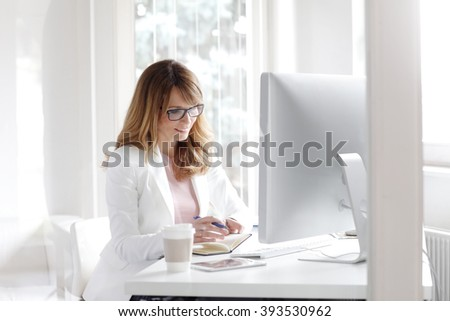 Portrait of executive businesswoman sitting at office in front of computer and working on business plan. - stock photo