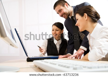 Portrait of executive employees looking at laptop monitor and discussing new project