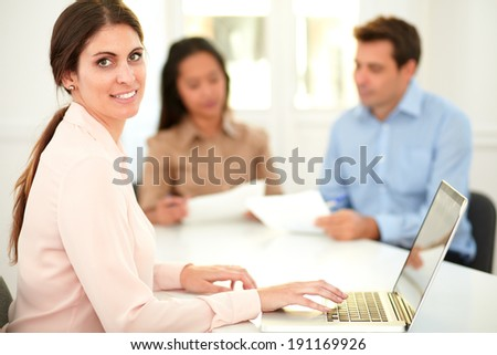 Portrait of executive lady working on her laptop while smiling at you and sitting with colleagues on office desk