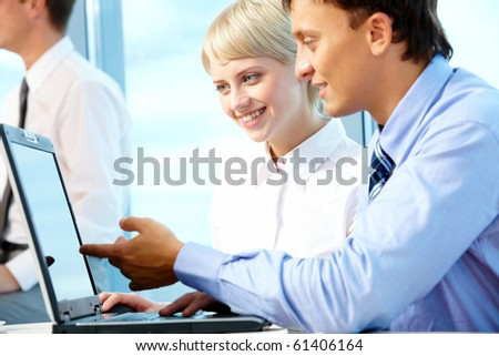 Portrait of executive partners looking at laptop during meeting - stock photo