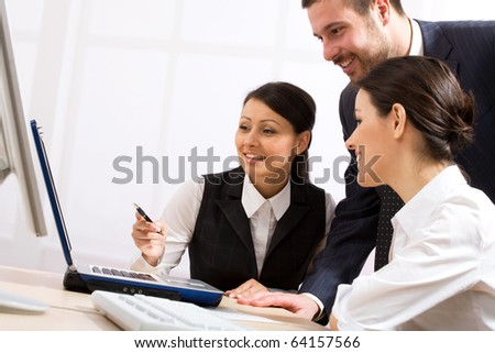 Portrait of executive partners looking at laptop during meeting
