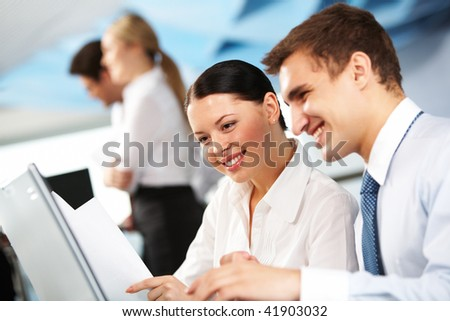 Portrait of executive partners looking at laptop on background of their partners