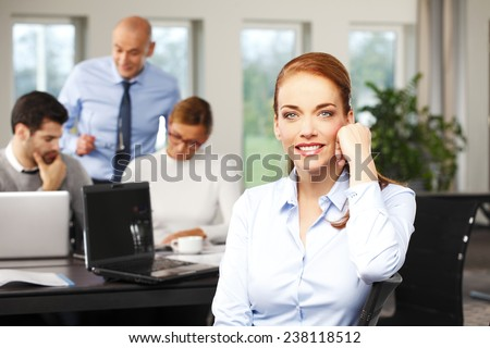 Portrait of executive sales woman sitting at office, while business people working at background. Teamwork.  - stock photo