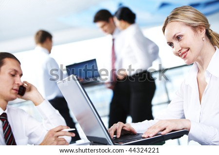 Portrait of executive secretary working with laptop on background of interacting partners