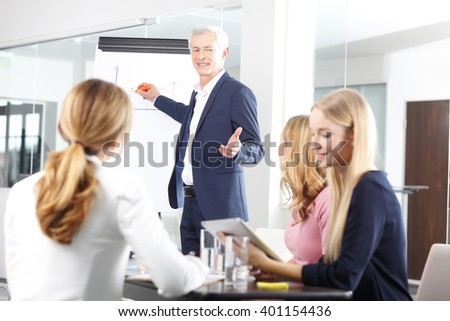 Portrait of executive senior businessman presenting th new business plan to his colleagues at meeting. - stock photo