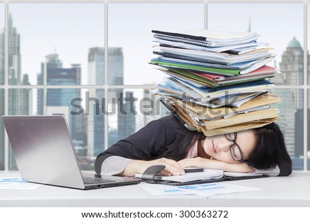 Portrait of exhausted businesswoman sleeping in the office with laptop on desk and paperwork over head - stock photo