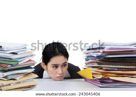 Portrait of exhausted female worker looking at pile of documents, isolated on white background - stock photo
