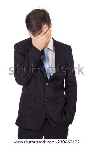 Portrait of exhausted young businessman covering his face with hands over white background - stock photo