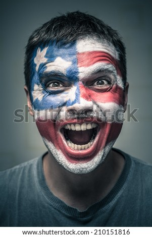 Portrait of exited man with US flag painted on face.