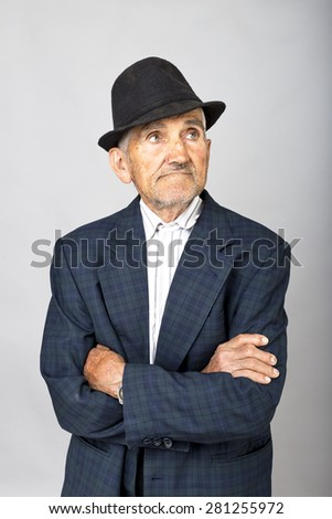 Portrait of expressive old  man with arms folded over gray background - stock photo